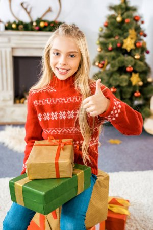 beautiful happy child sitting on stacked christmas gift boxes showing thumb up