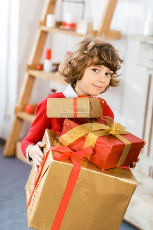 adorable happy kid holding stack of christmas gift boxes