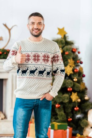 handsome bearded man in christmas sweater showing thumb up at camera