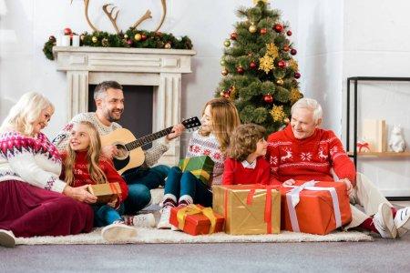 Photo pour Héhé, assis sur des chansons à la guitare ensemble et écoute étage à la maison à Noël - image libre de droit