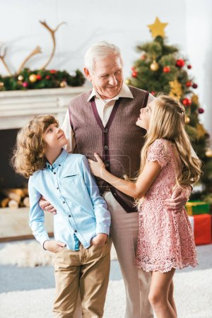 happy grandfather embracing kids in christmas decorated living room at home