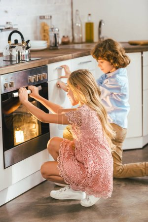 adorable kids looking at baking oven at kitchen