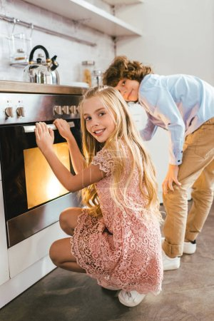 happy adorable siblings standing near oven at kitchen