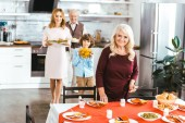 grandparents with adult daughter and little grandson serving table for thanksgiving dinner