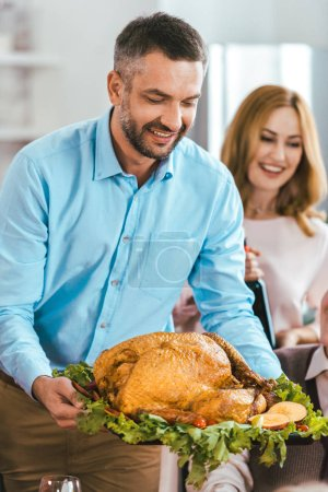 happy young man serving turkey on thanksgiving table