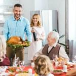Happy family with turkey celebrating thanksgiving ...