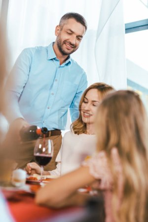 handsome man pouring wine for his woman during holiday dinner