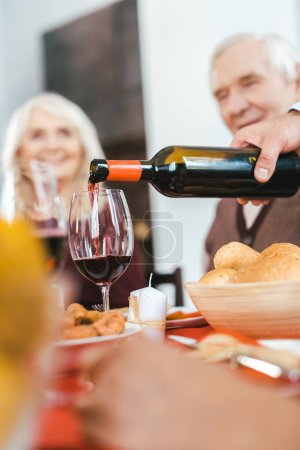cropped shot of senior couple sitting at holiday table while man pouring wine on foreground