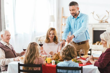 happy family having delicious thanksgiving dinner together at home while father cutting turkey