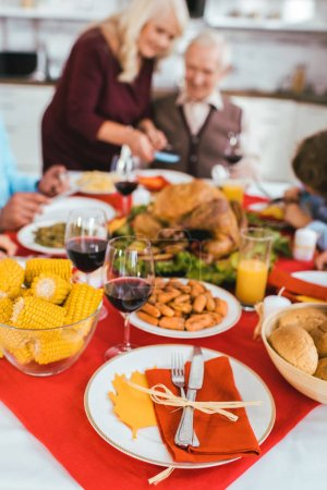 thanksgiving dinner table with various tasty dishes and seniour couple sitting blurred on background