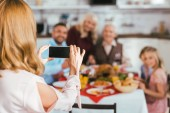 rear view of woman taking photo of her family during thanksgiving dinner