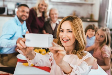 Photo for Happy young woman taking selfie with her family during thanksgiving dinner - Royalty Free Image