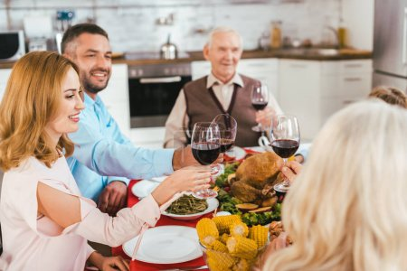 happy family clinking glasses of wine during thanksgiving dinner
