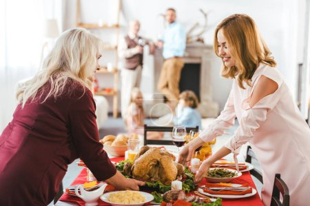 smiling young and senior women serving thanksgiving day table while men and kids standing blurred on background