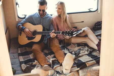 handsome man playing on guitar while hippie girl holding vinyl record inside trailer