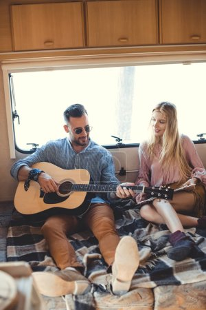 handsome man playing on guitar while girlfriend holding vinyl record inside trailer