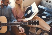 hippie couple with acoustic guitar and vinyl records sitting inside trailer