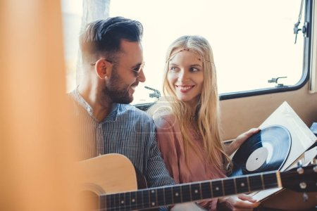 beautiful hippie couple resting inside trailer with acoustic guitar and  vinyl record