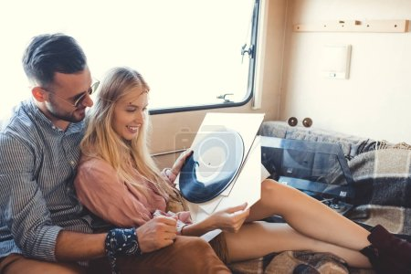 beautiful hippie couple choosing vinyl records inside campervan with vinyl player