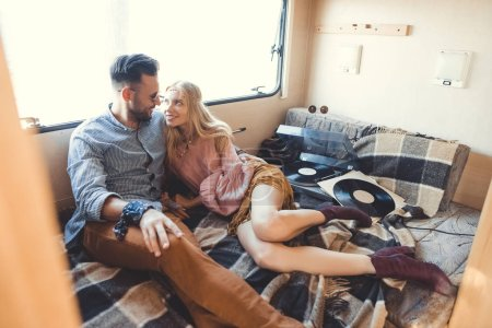 beautiful hippie couple relaxing inside campervan and listening vinyl records