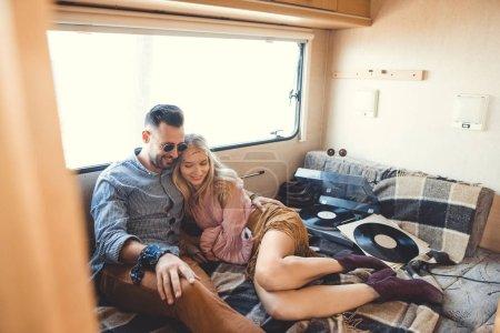 hippie couple listening music on vinyl records inside trailer