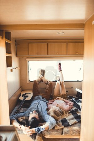 young hippie couple resting inside trailer with guitar and vinyl player