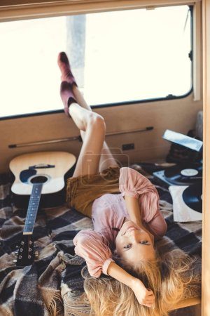 beautiful hippie girl lying inside campervan with acoustic guitar and vinyl player