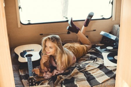 young woman lying inside campervan with acoustic guitar and vinyl player