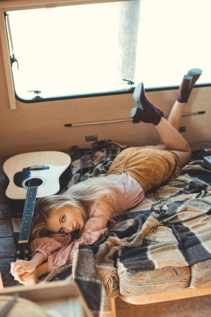 attractive hippie girl lying inside camper van with acoustic guitar