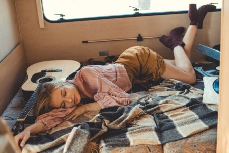 hippie girl sleeping inside trailer with acoustic guitar, vinyl player and records