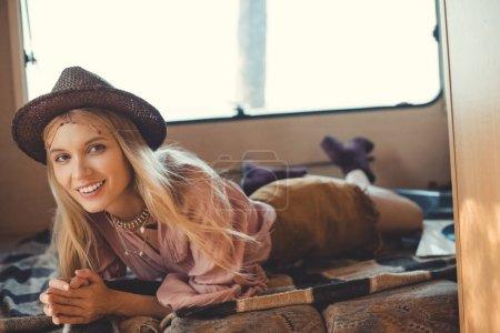smiling hippie girl lying inside camper van