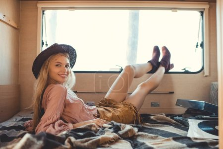 attractive hippie girl lying inside camper van with vinyl player and records