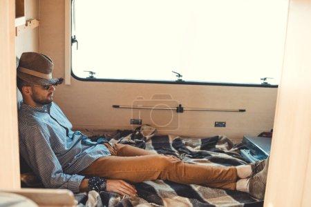 handsome man in hat resting inside of campervan with vinyl player