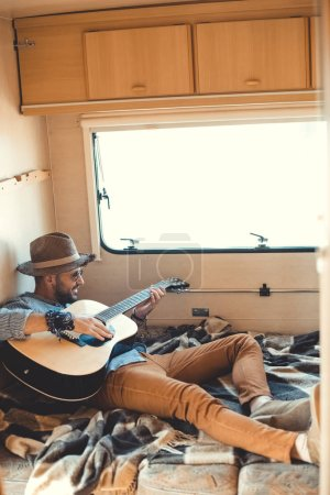 handsome man playing on acoustic guitar inside of trailer