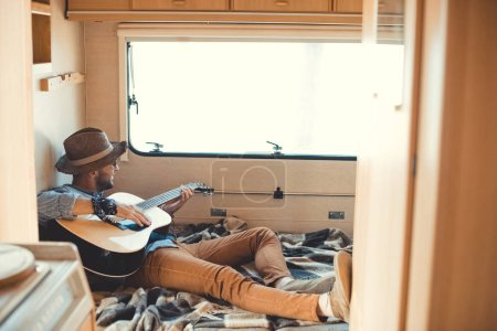 young man playing on acoustic guitar inside of campervan and looking at window
