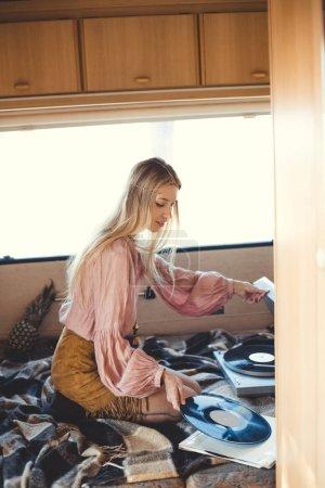 beautiful hippie girl putting vinyl record into player inside camper van
