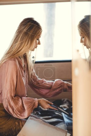 blonde hippie girl putting vinyl record into player inside camper van
