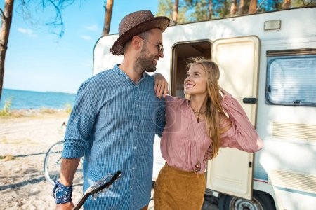 hippie couple hugging and walking near campervan