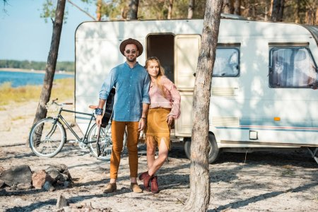 young couple of campers posing near trailer