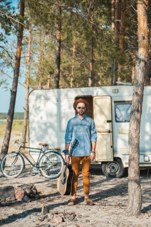 man holding acoustic guitar and standing at trailer with bicycle