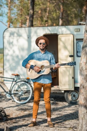 male guitarist playing on acoustic guitar near campervan with bike