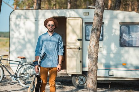happy man holding guitar and standing at trailer with bicycle
