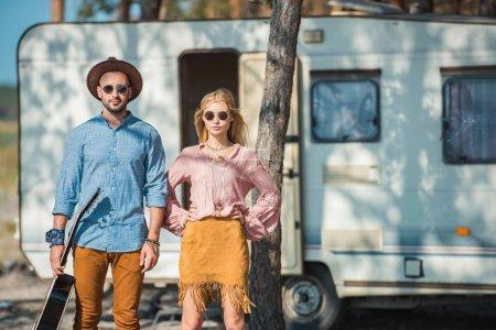 Photo pour Couple jeune hippie de campeurs posant près de remorque - image libre de droit