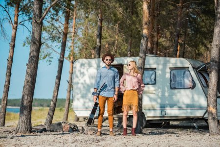 young hippie couple with acoustic guitar posing near campervan