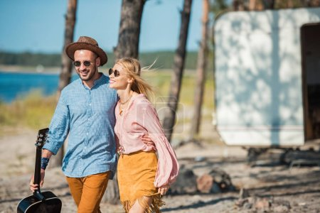 beautiful hippie couple in sunglasses hugging and walking with guitar near campervan