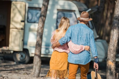back view of hippie couple hugging and holding guitar near campervan