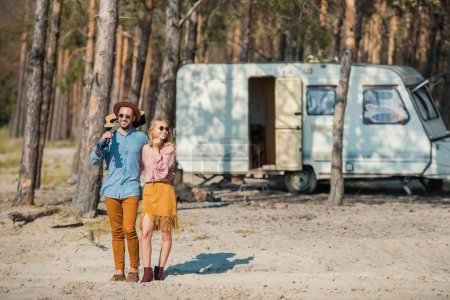 young hippie couple hugging and standing with guitar near campervan in forest