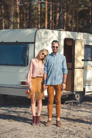 hippie couple in wreaths and sunglasses holding hands and posing near camper van