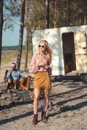 beautiful hippie girl in wreath, man sitting near campervan in forest behind