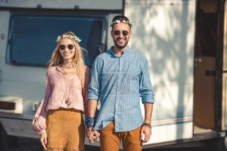 hippie couple holding hands and posing near trailer